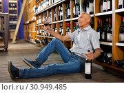 Купить «Portrait of senior man sitting on floor in winery tasting room, drinking red wine», фото № 30949485, снято 8 мая 2019 г. (c) Яков Филимонов / Фотобанк Лори