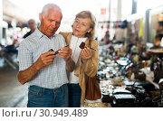 Купить «Mature couple choose smoking pipe on flea market», фото № 30949489, снято 11 мая 2019 г. (c) Яков Филимонов / Фотобанк Лори