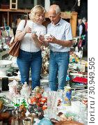 Купить «Mature family couple choosing vintage dishes on street market», фото № 30949505, снято 11 мая 2019 г. (c) Яков Филимонов / Фотобанк Лори