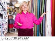 Купить «Positive mature female seller offering curtain in store», фото № 30949661, снято 17 января 2018 г. (c) Яков Филимонов / Фотобанк Лори