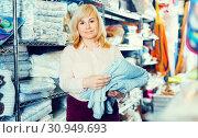 Купить «Portrait of mature woman holding cotton bed cover», фото № 30949693, снято 17 января 2018 г. (c) Яков Филимонов / Фотобанк Лори