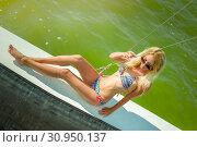 Купить «Young beautiful slim sexy girl in bikini and pareo is resting on cruise on a private sailing yacht», фото № 30950137, снято 25 июля 2017 г. (c) katalinks / Фотобанк Лори