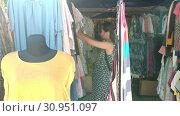 Купить «Woman choosing clothes at the market», видеоролик № 30951097, снято 1 июня 2019 г. (c) Илья Шаматура / Фотобанк Лори