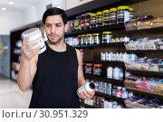 Купить «Serious young muscular man choosing sport nutrition products in shop», фото № 30951329, снято 28 марта 2018 г. (c) Яков Филимонов / Фотобанк Лори