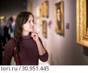 Купить «Woman attentively looking at paintings in art museum», фото № 30951445, снято 17 ноября 2019 г. (c) Яков Филимонов / Фотобанк Лори