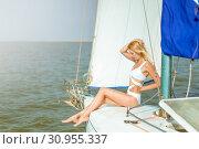 Купить «Young beautiful slim sexy girl in bikini and pareo is resting on cruise on a private sailing yacht», фото № 30955337, снято 25 июля 2017 г. (c) katalinks / Фотобанк Лори