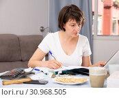 Купить «Woman with documents while working at laptop at home», фото № 30968505, снято 19 июня 2019 г. (c) Яков Филимонов / Фотобанк Лори