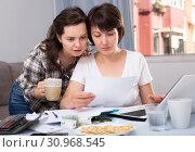 Купить «Woman with documents and coffee at kitchen table with laptop», фото № 30968545, снято 19 июня 2019 г. (c) Яков Филимонов / Фотобанк Лори