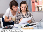 Купить «Two smiling women sitting at home table with laptop», фото № 30968557, снято 19 июня 2019 г. (c) Яков Филимонов / Фотобанк Лори