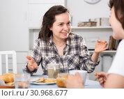 Купить «Two smiling women drinking tea with cookies in the kitchen», фото № 30968677, снято 19 июня 2019 г. (c) Яков Филимонов / Фотобанк Лори