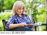 Купить «Portrait of mature woman sitting on bench and reading book in garden», фото № 30969597, снято 17 июня 2016 г. (c) Яков Филимонов / Фотобанк Лори