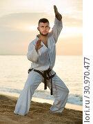 Купить «Ordinary guy practising karate kata poses», фото № 30970477, снято 19 июля 2017 г. (c) Яков Филимонов / Фотобанк Лори