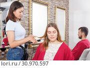 Купить «Young girl hairstylist working with female's hair in salon», фото № 30970597, снято 25 апреля 2018 г. (c) Яков Филимонов / Фотобанк Лори