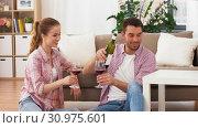 Купить «happy couple drinking red wine at home», видеоролик № 30975601, снято 10 июня 2019 г. (c) Syda Productions / Фотобанк Лори