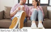 Купить «feet of couple drinking coffee at home on table», видеоролик № 30975705, снято 10 июня 2019 г. (c) Syda Productions / Фотобанк Лори