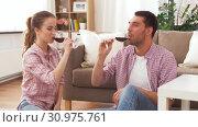 Купить «happy couple drinking red wine at home», видеоролик № 30975761, снято 10 июня 2019 г. (c) Syda Productions / Фотобанк Лори