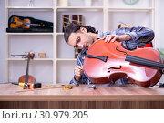 Купить «Young handsome repairman repairing cello», фото № 30979205, снято 4 апреля 2019 г. (c) Elnur / Фотобанк Лори