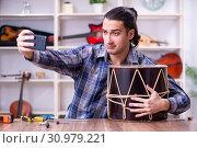Купить «Young handsome repairman repairing drum», фото № 30979221, снято 4 апреля 2019 г. (c) Elnur / Фотобанк Лори