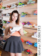 Купить «Young sportswoman choosing professional shoes», фото № 30984913, снято 15 мая 2017 г. (c) Яков Филимонов / Фотобанк Лори