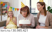 Купить «mother, daughter, grandmother with birthday cake», видеоролик № 30985421, снято 14 июня 2019 г. (c) Syda Productions / Фотобанк Лори