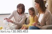 Купить «mother, daughter and grandmother having tea party», видеоролик № 30985453, снято 14 июня 2019 г. (c) Syda Productions / Фотобанк Лори