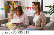 Купить «mother, daughter, grandmother with birthday cake», видеоролик № 30985513, снято 14 июня 2019 г. (c) Syda Productions / Фотобанк Лори