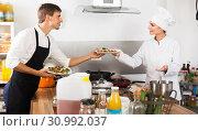 Smiling woman cook giving salad to waitress. Стоковое фото, фотограф Яков Филимонов / Фотобанк Лори