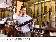Купить «Brunette male hunter choosing shotgun in store», фото № 30992141, снято 11 декабря 2017 г. (c) Яков Филимонов / Фотобанк Лори