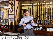 Купить «Handsome adult male in hunting shop with rifle in hands», фото № 30992153, снято 11 декабря 2017 г. (c) Яков Филимонов / Фотобанк Лори