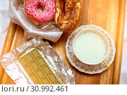 Купить «Focus on green chocolate with the Chinese matcha tea, antique porcelain cup with whipped cream and pretzels with iced donuts», фото № 30992461, снято 9 февраля 2019 г. (c) katalinks / Фотобанк Лори
