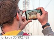 """Купить «Молодой мужчина в очках фотографирует праздничный концерт на ВДНХ. На экране смартфона изображение летней открытой сцены и павильона № 1 """"Центральный""""», фото № 30992485, снято 30 апреля 2019 г. (c) Наталья Николаева / Фотобанк Лори"""