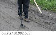 Купить «Мужчина с металлоискателем идет по дороге, сканирует грунт», видеоролик № 30992605, снято 20 июня 2019 г. (c) А. А. Пирагис / Фотобанк Лори
