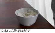 Купить «Closeup of woman eating rice from bowl», видеоролик № 30992613, снято 20 июня 2019 г. (c) Ekaterina Demidova / Фотобанк Лори