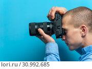 Купить «Male photographer examining his new camera», фото № 30992685, снято 16 июля 2020 г. (c) Pavel Biryukov / Фотобанк Лори