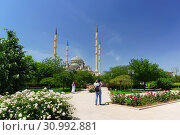 """Купить «Люди гуляют в парке возле мечети """"Сердце Чечни"""" имени Ахмата Кадырова в Грозном. Солнечный летний день», фото № 30992881, снято 2 июня 2019 г. (c) Наталья Гармашева / Фотобанк Лори"""