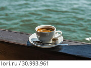 A small white porcelain espresso cup on a saucer with a teaspoon and two pieces of sugar. Стоковое фото, фотограф katalinks / Фотобанк Лори
