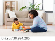 Купить «mother and baby playing with toy blocks at home», фото № 30994285, снято 22 марта 2019 г. (c) Syda Productions / Фотобанк Лори