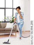 Купить «african american woman with vacuum cleaner at home», фото № 30994289, снято 7 апреля 2019 г. (c) Syda Productions / Фотобанк Лори