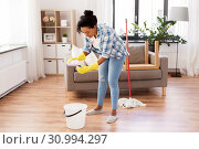 Купить «african woman or housewife cleaning floor at home», фото № 30994297, снято 7 апреля 2019 г. (c) Syda Productions / Фотобанк Лори