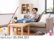 Купить «woman calling on smartphone after home cleaning», фото № 30994301, снято 7 апреля 2019 г. (c) Syda Productions / Фотобанк Лори