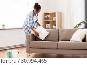 Купить «african american woman arranging sofa cushions», фото № 30994465, снято 7 апреля 2019 г. (c) Syda Productions / Фотобанк Лори