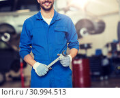 auto mechanic or smith with wrench at car workshop. Стоковое фото, фотограф Syda Productions / Фотобанк Лори