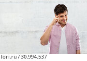 Купить «smiling young man pointing finger to his head», фото № 30994537, снято 3 февраля 2019 г. (c) Syda Productions / Фотобанк Лори