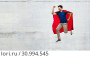 Купить «man in red superhero cape jumping over concrete», фото № 30994545, снято 3 февраля 2019 г. (c) Syda Productions / Фотобанк Лори
