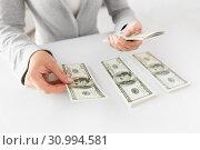 Купить «close up of woman hands counting us dollar money», фото № 30994581, снято 2 июля 2015 г. (c) Syda Productions / Фотобанк Лори