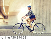 Купить «young hipster man with bag riding fixed gear bike», фото № 30994681, снято 15 июня 2016 г. (c) Syda Productions / Фотобанк Лори