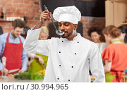 chef tasting food from ladle at cooking class. Стоковое фото, фотограф Syda Productions / Фотобанк Лори