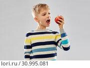 Купить «boy in striped pullover eating red apple», фото № 30995081, снято 9 марта 2019 г. (c) Syda Productions / Фотобанк Лори