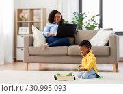 Купить «baby playing toy blocks and mother using laptop», фото № 30995093, снято 22 марта 2019 г. (c) Syda Productions / Фотобанк Лори