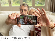 Active senior couple sitting on sofa and taking selfie in a comfortable home. Стоковое фото, агентство Wavebreak Media / Фотобанк Лори